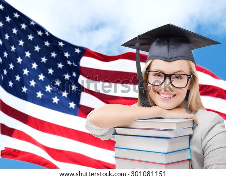 education, high school, knowledge and people concept - picture of happy student girl or woman in trencher cap with stack of books over american flag background - stock photo