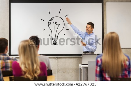 education, high school, teaching, idea and people concept - group of students and happy teacher with notepad showing light bulb drawing on white board in classroom - stock photo