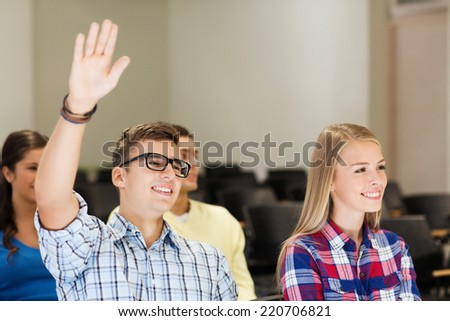 education, high school, teamwork and people concept - group of smiling students raising hand in lecture hall - stock photo