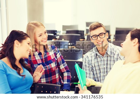 education, high school, teamwork and people concept - group of smiling students with notebook sitting in lecture hall and talking - stock photo