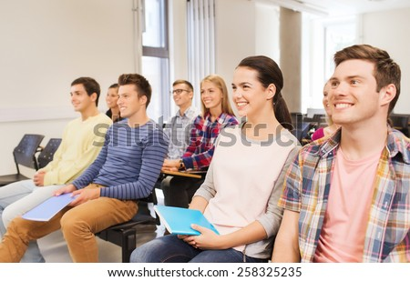 education, high school, teamwork and people concept - group of smiling students with notepads sitting in lecture hall
