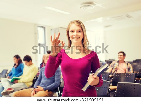 education, high school, teamwork and people concept - group of smiling students with notepads showing ok gesture in lecture hall - stock photo