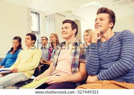 education, high school, teamwork and people concept - group of smiling students with notepads sitting in lecture hall - stock photo