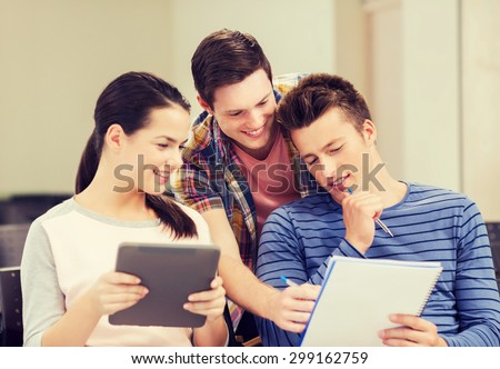 education, high school, teamwork and people concept - group of smiling students with tablet pc computer and notebook sitting in lecture hall