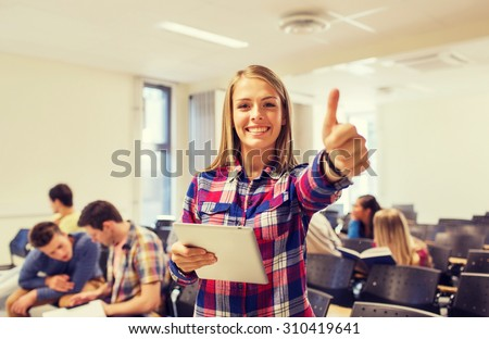 education, high school, teamwork and people concept - group of smiling students with tablet pc computer howing thumbs up in lecture hall - stock photo