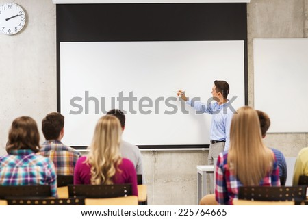 education, high school, teamwork and people concept - smiling teacher standing in front of students and writing something on white board in classroom