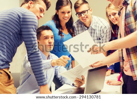 education, high school, technology and people concept - group of smiling students and teacher with papers, laptop computer in classroom - stock photo
