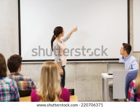 education, high school, technology and people concept - smiling student girl standing in front of white board and teacher with laptop computer in classroom - stock photo