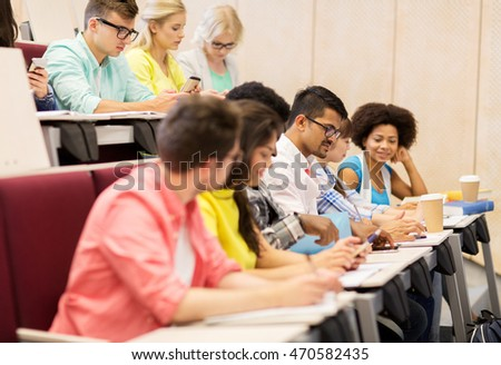 education, high school, university, learning and people concept - group of international students with notebooks and coffee writing test in lecture hall