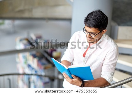 education, high school, university, learning and people concept - happy hindu student boy or young man reading book on stairs at library