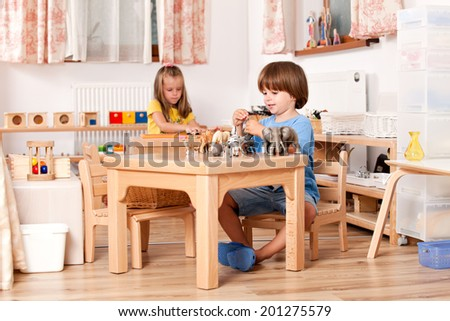 Education image from a kindergarten: child playing with his animal toys at his table - stock photo