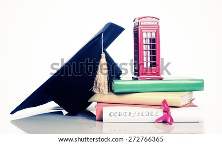 education in Great Britain Concept. Stack of books, mortarboard, diploma and red phone box - symbol of England