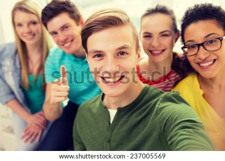 education, leisure and technology concept - five smiling students taking selfie at school - stock photo