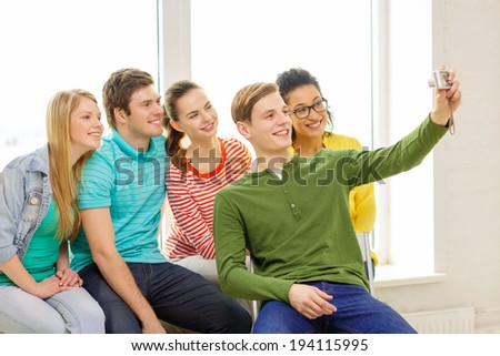 education, leisure and technology concept - five smiling students taking selfie with digital camera at school - stock photo