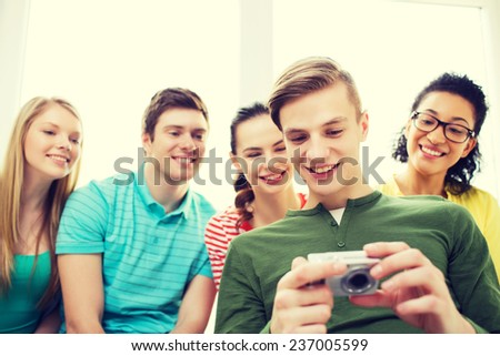 education, leisure and technology concept - five smiling students with digital camera at school - stock photo