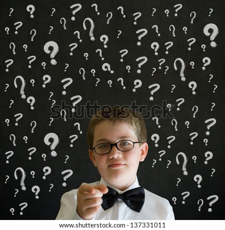Education needs you thinking boy dressed up as business man with chalk questions marks on blackboard background - stock photo