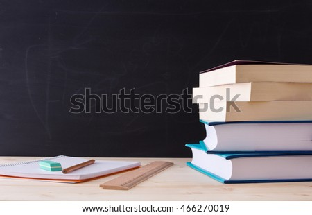 Education, notepad, pencil, eraser, ruler, and books on wooden table with blackboard