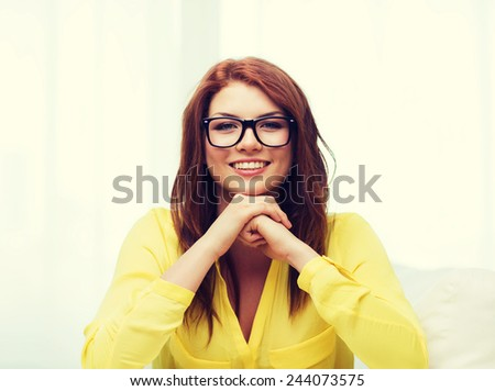 education, people and happiness concept - smiling teenage girl in eyeglasses at home - stock photo