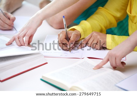 education, people and school concept - close up of students hands with textbooks writing to notebooks at school - stock photo