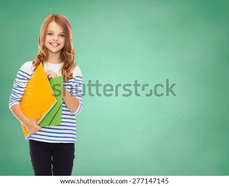 education, people, children and school concept - happy girl holding colorful folders over green board background - stock photo