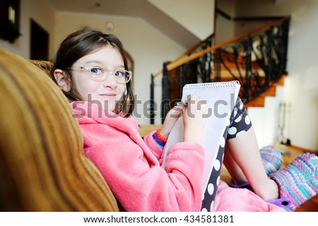 education, people, children and school concept - happy student girl sitting at sofa in cozy home clothes and doing her homework - stock photo