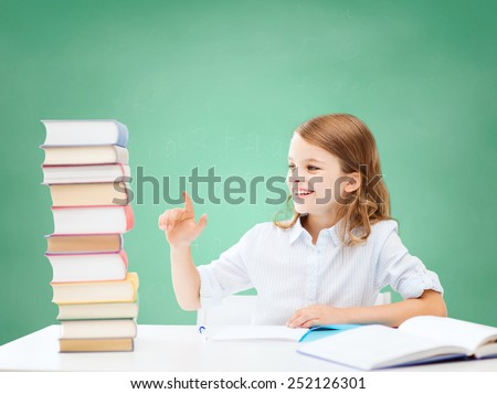 education, people, children and school concept - happy student girl sitting at table and counting books over green chalk board background - stock photo