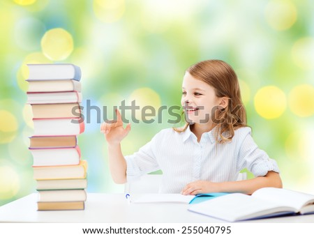 education, people, children and school concept - happy student girl sitting at table and counting books over green lights background - stock photo