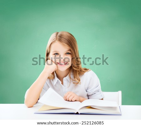 education, people, children and school concept - little student girl sitting at table with book over green chalk board background - stock photo