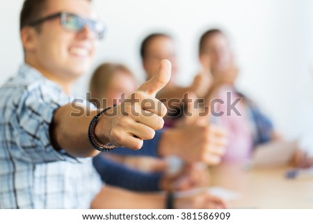 education, people, friendship and learning concept - group of happy high school students or classmates showing thumbs up - stock photo