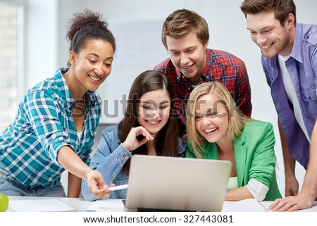 education, people, friendship, technology and learning concept - group of happy international high school students or classmates with laptop computer in classroom - stock photo