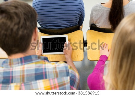 education, people, technology and learning concept - close up of high school students or classmates with tablet pc computer blank screen at lecture - stock photo