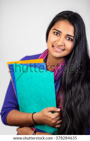 Education portrait of an pretty india woman holding notebooks on bright background  - stock photo