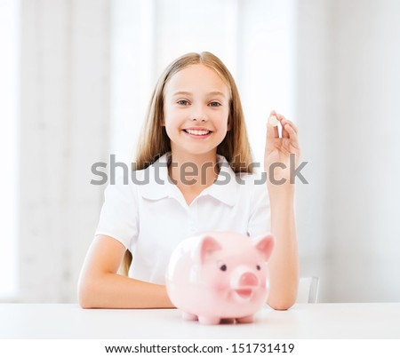 education, school and money saving concept - child putting coins into piggy bank - stock photo