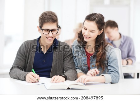 education, school and people concept - two teenagers with notebooks and book at school