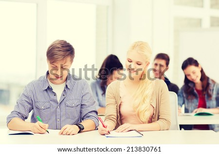 education, school and people concept - two teenagers with notebooks at school