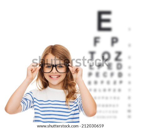 education, school and vision concept - smiling cute little girl with black eyeglasses - stock photo