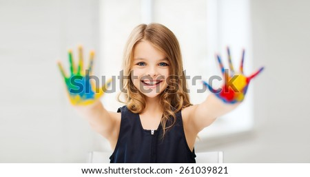 education, school, art and painitng concept - little student girl showing painted hands at school - stock photo