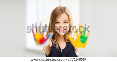 education, school, art and painitng concept - smiling little student girl showing painted hands at school - stock photo