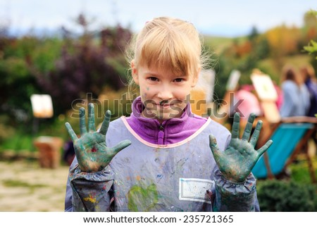education, school, art and painting concept - smiling little student girl showing painted hands at workshop - stock photo