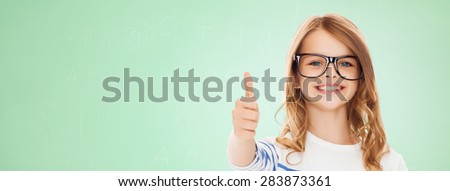 education, school, childhood, people and vision concept - smiling cute little girl with black eyeglasses showing thumbs up gesture over green chalk board background - stock photo