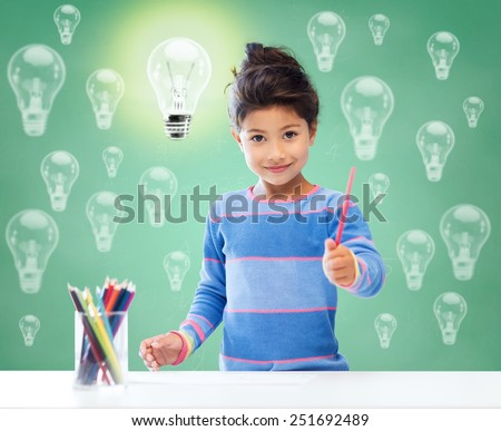 education, school, children, creativity and happy people concept - happy little girl drawing with coloring pencils over green chalk board background and light bulbs - stock photo