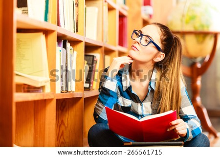 Education school concept. Clever female student hair ponytail girl blue glasses sitting on floor in college library with stack books. Indoor - stock photo