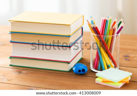education, school, creativity and object concept - close up of crayons or color pencils with books, stickers and sharpener on wooden table