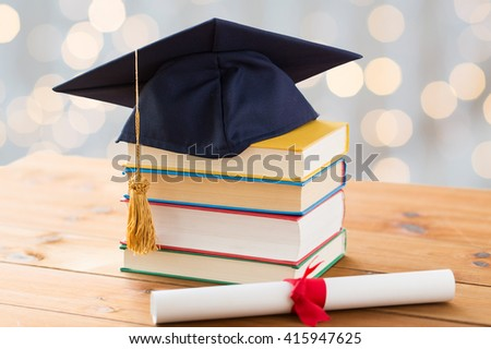 education, school, graduation and knowledge concept - close up of books and mortarboard with diploma on wooden table over holidays lights background - stock photo