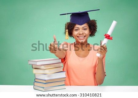 education, school, graduation, gesture and people concept - happy smiling african american student girl in bachelor cap with books and diploma showing thumbs up over green chalk board background - stock photo