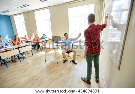 education, school, learning and people concept - student boy showing something on blank white board and teacher in classroom - stock photo