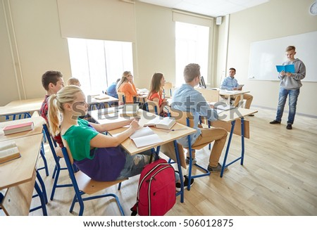 education, school, learning, examination and people concept - student boy with notebook and teacher in classroom