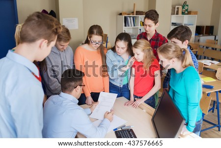 education, school, learning, teaching and people concept - group of students and teacher checking tests at school - stock photo