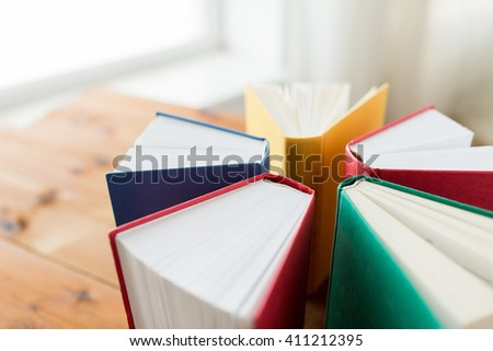 education, school, literature, reading and knowledge concept - close up of books on wooden table - stock photo