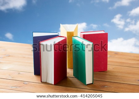 education, school, literature, reading and knowledge concept - close up of books on wooden table over blue sky and clouds background - stock photo